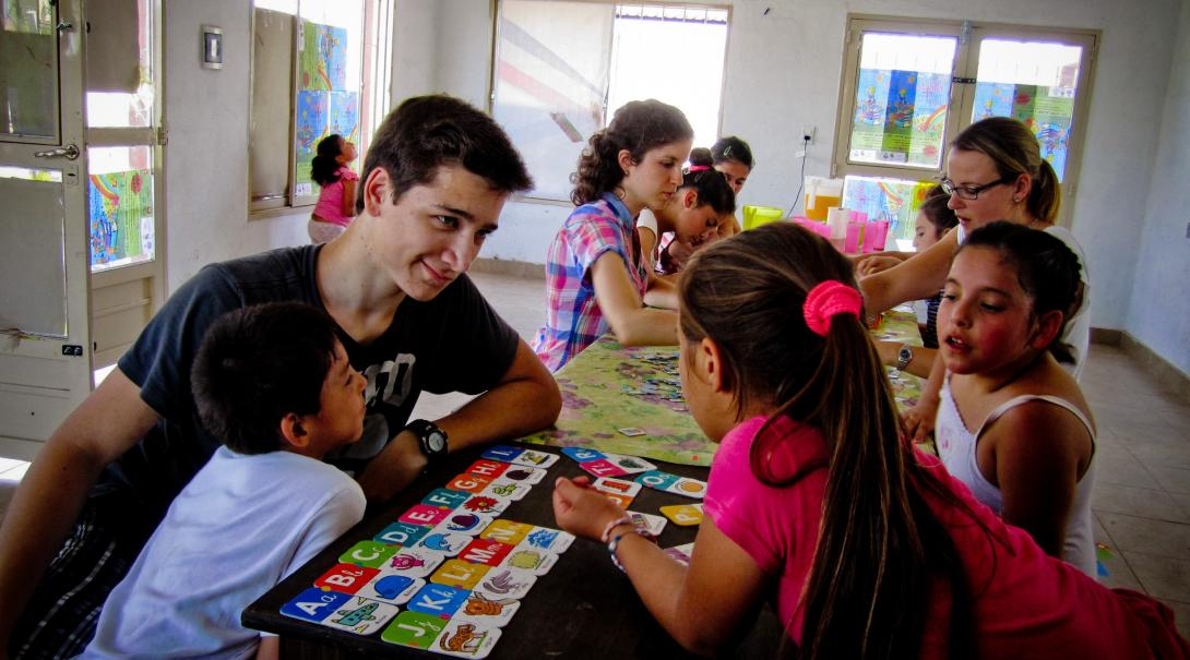 A teenager volunteering in Argentina teach basic English to children.